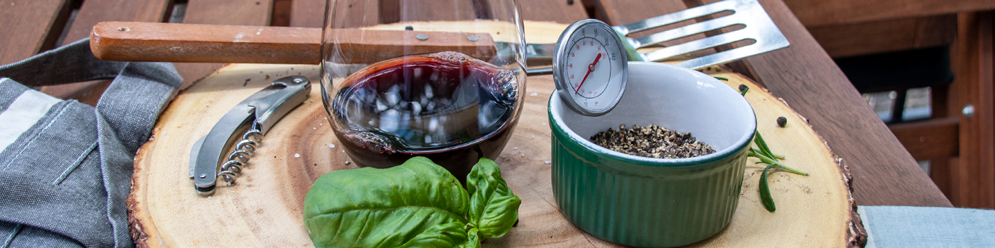 Glass of red wine, basil leaf, timer, and bowl of spices ready to bbq