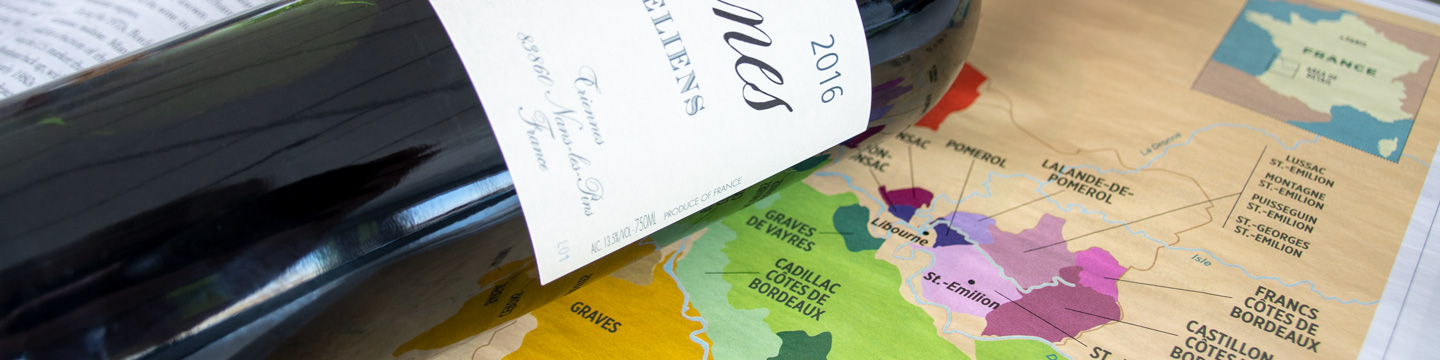 Bottle of Bordeaux red wine placed on a map of the Bordeaux wine region