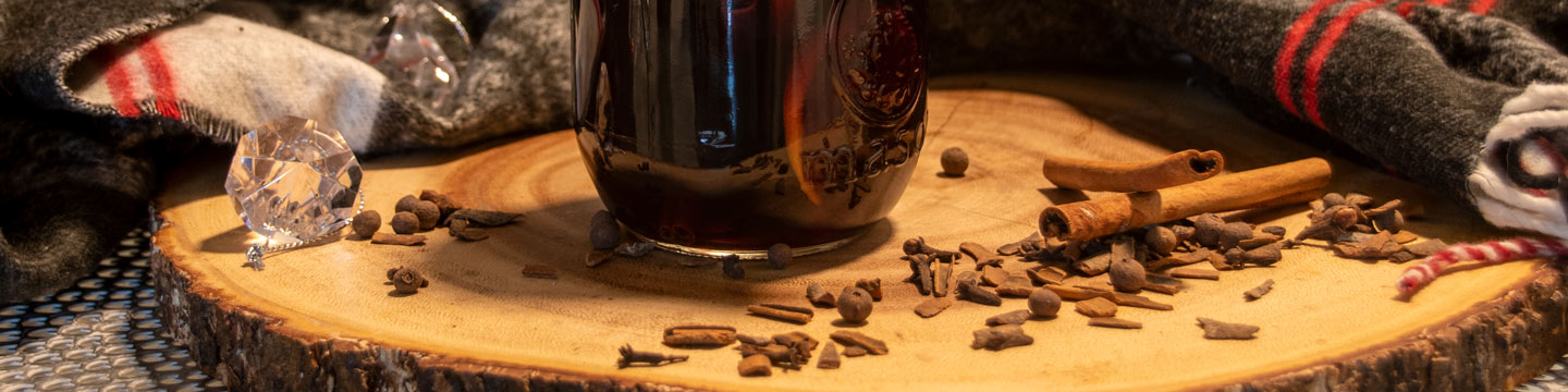 Glass of mulled wine on a wood block, surrounded by ingredients like cinnamon sticks and clove.