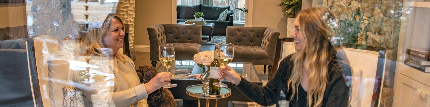 A mother and daughter enjoying white wine together.