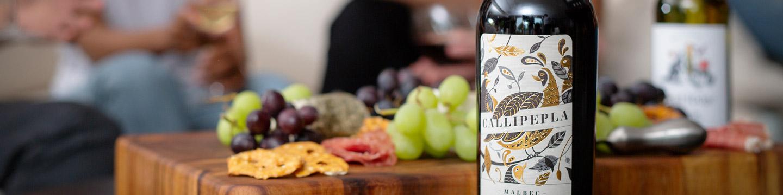 A Callipepla Malbec wine bottle sitting in front of a charcuterie board.