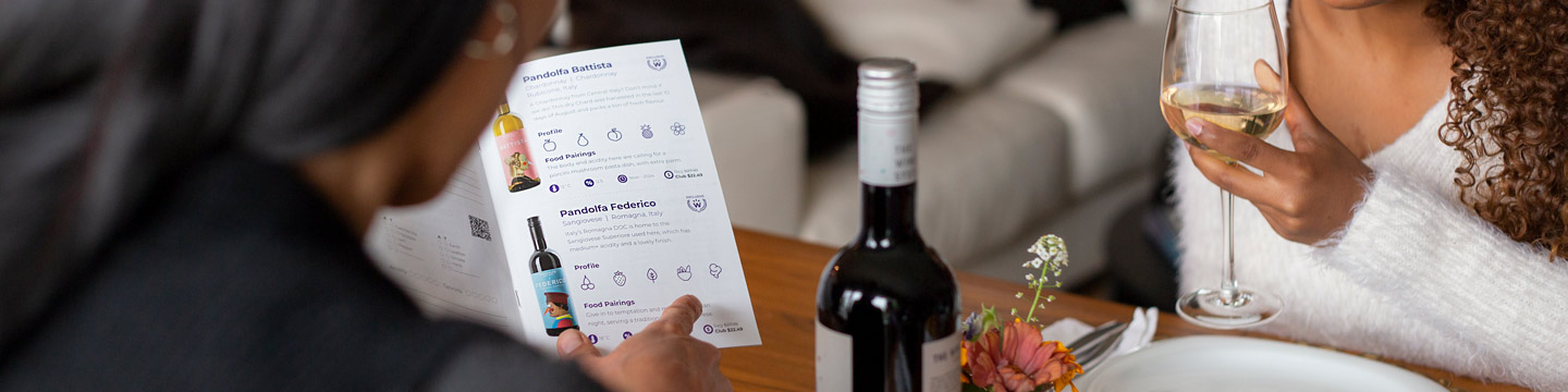 Two women using the WineCollective tasting guide as they taste their monthly wine gifts for her.