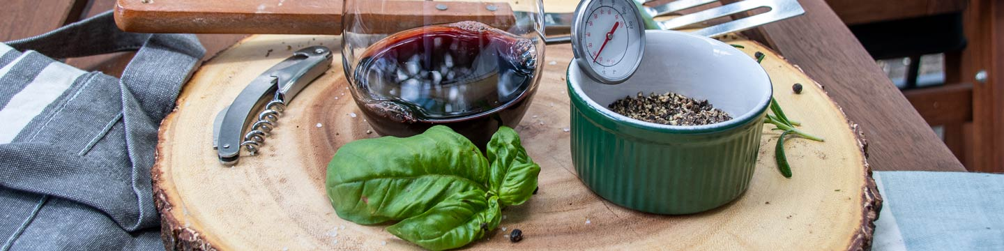 A stem-less glass of red wine surrounded by spices for cooking and a corkscrew.