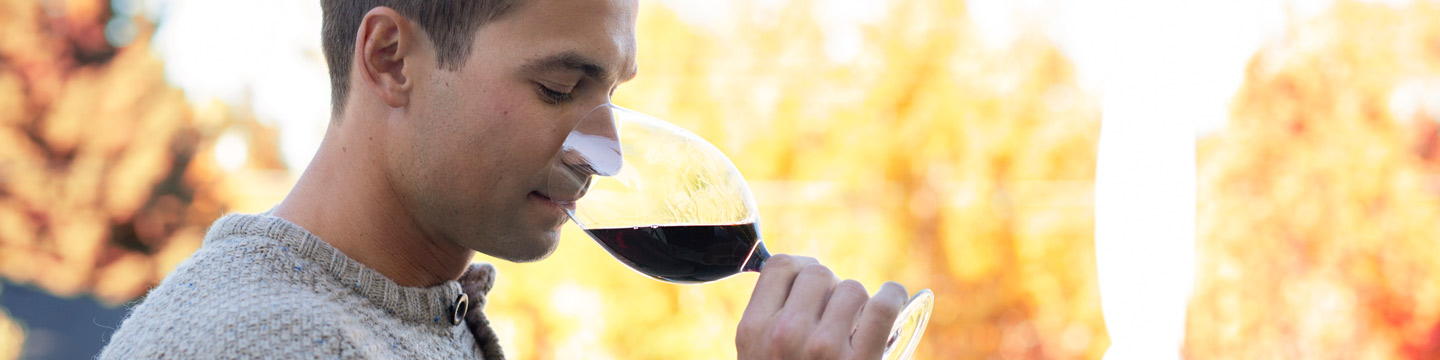 Profile view of a man taking a sip of red wine.