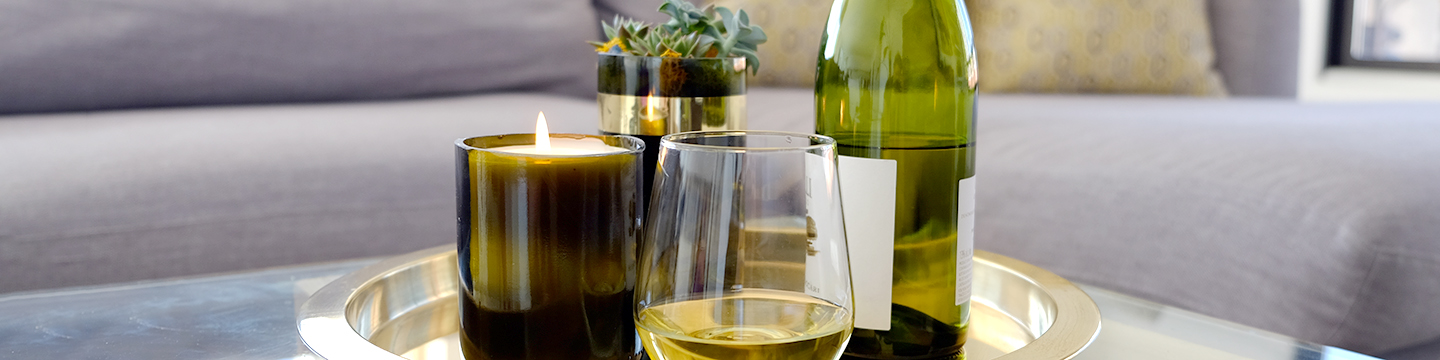 A glass-cut wine bottle holding a candle, and another holding a succulent, decorating a coffee table.