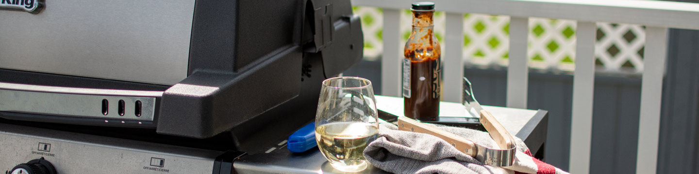 A glass of wine from WineCollective accompanied by a barbecue for Father's Day festivities - a father's day gift idea.