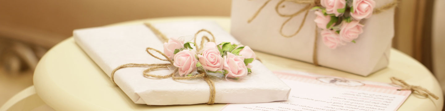 white paper wrapped wedding gifts topped with pale pink flowers on a table