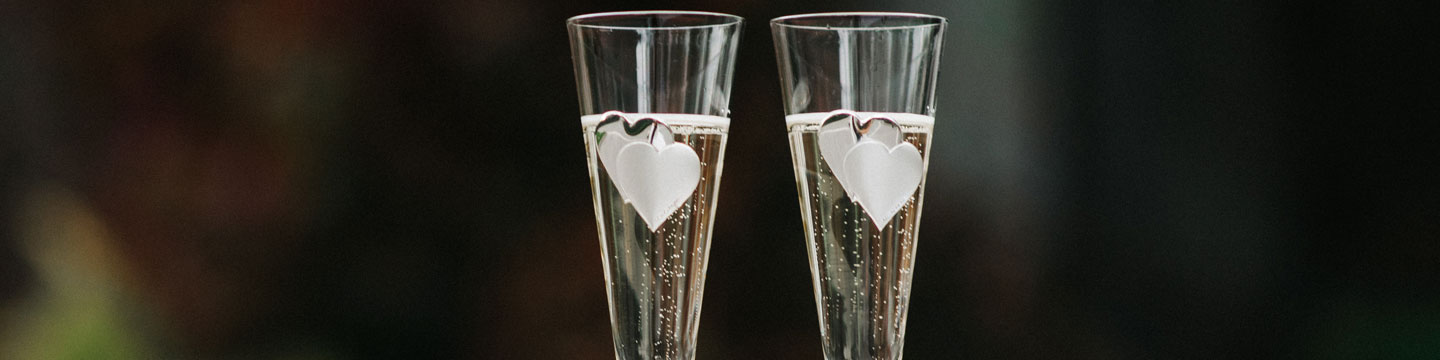 two champagne flutes with etched hearts on them