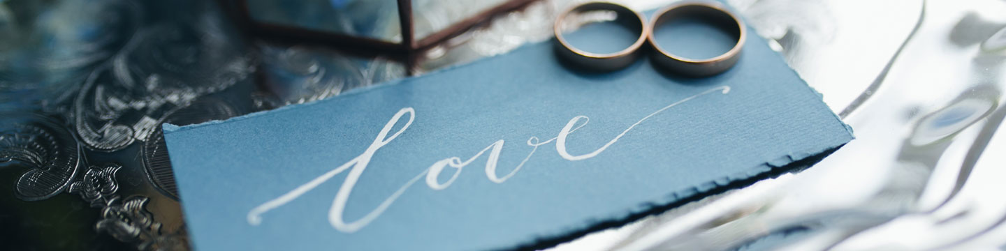 """Dark coloured paper wedding invitation with """"love"""" written on it, topped with two wedding bands"""