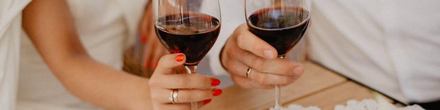 A bride and groom holding two glasses of red wine.