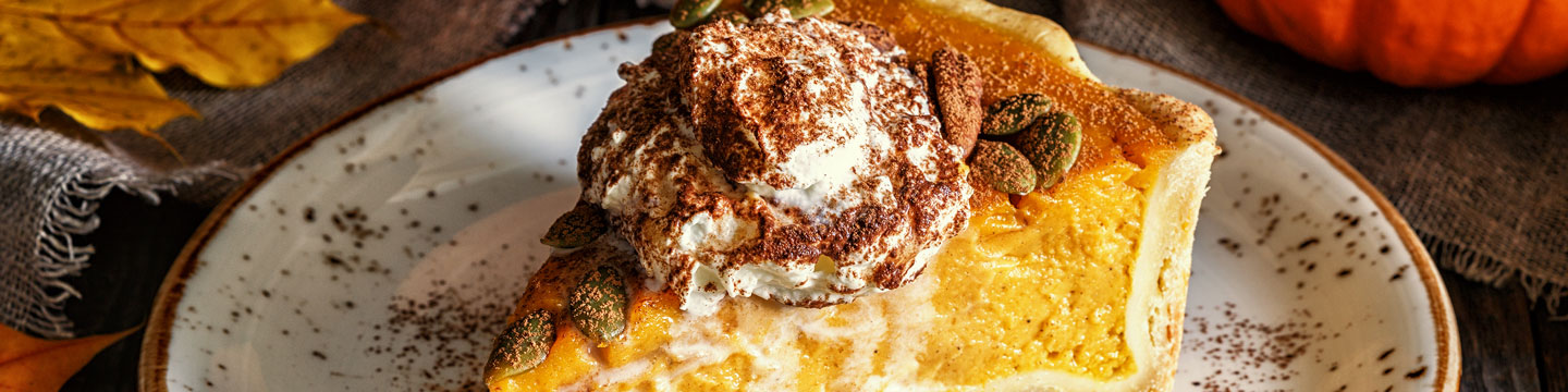 A slice of pumpkin pie with whipped cream.